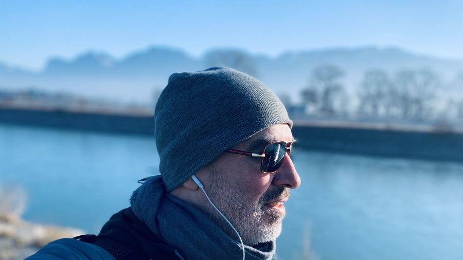 Close-up of man wearing sunglasses and knit hat standing outdoors during winter