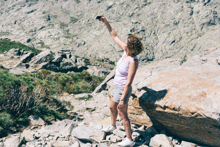 Woman hiker taking a selfie on top of the mountain Balance Beauty In Nature Casual Clothing Day Freedom Full Length Hiking Hikingadventures Landscape Leisure Activity Lifestyles Mountain Nature Non-urban Scene Outdoors Relaxing Rock Rock Formation Scenics Selfie Sky Tranquil Scene Tranquility Vacations Woman