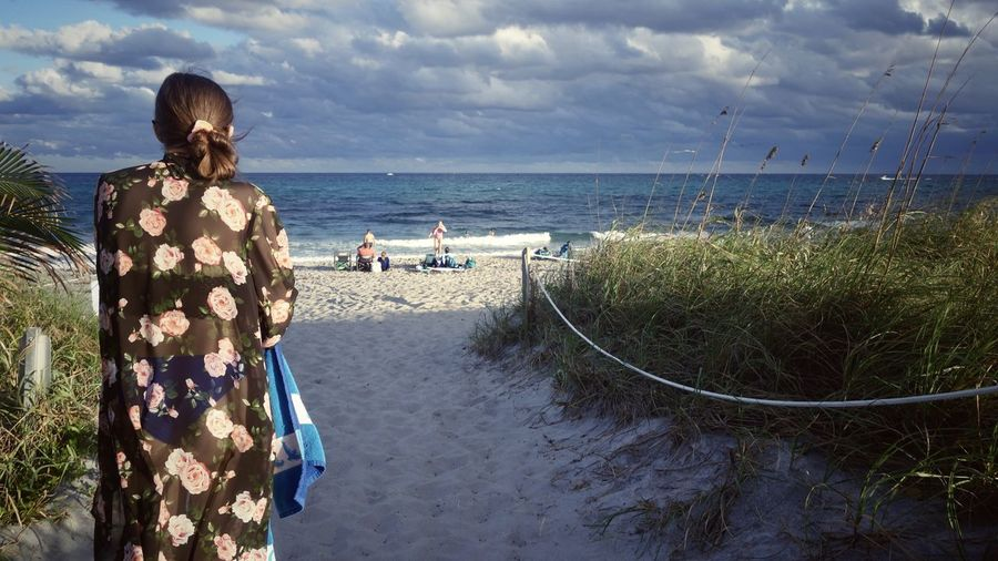 Rear view of teenager girl looking at sea shore against sky