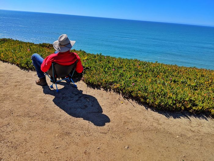 Can't get much better than this! man in red and hat sitting in chair on sandstone cliff by the ocean. Beach Chair Jacket White Hat Cowboy Hat Shadow Chair Lounge Sandstone Golden Blue Dramatic Headlands Overlook Contemplating Background Zen Therapeutic Soil Sitting Full Length Shadow Sunlight Agriculture Sky Hiker Ocean Coast Calm Scenics