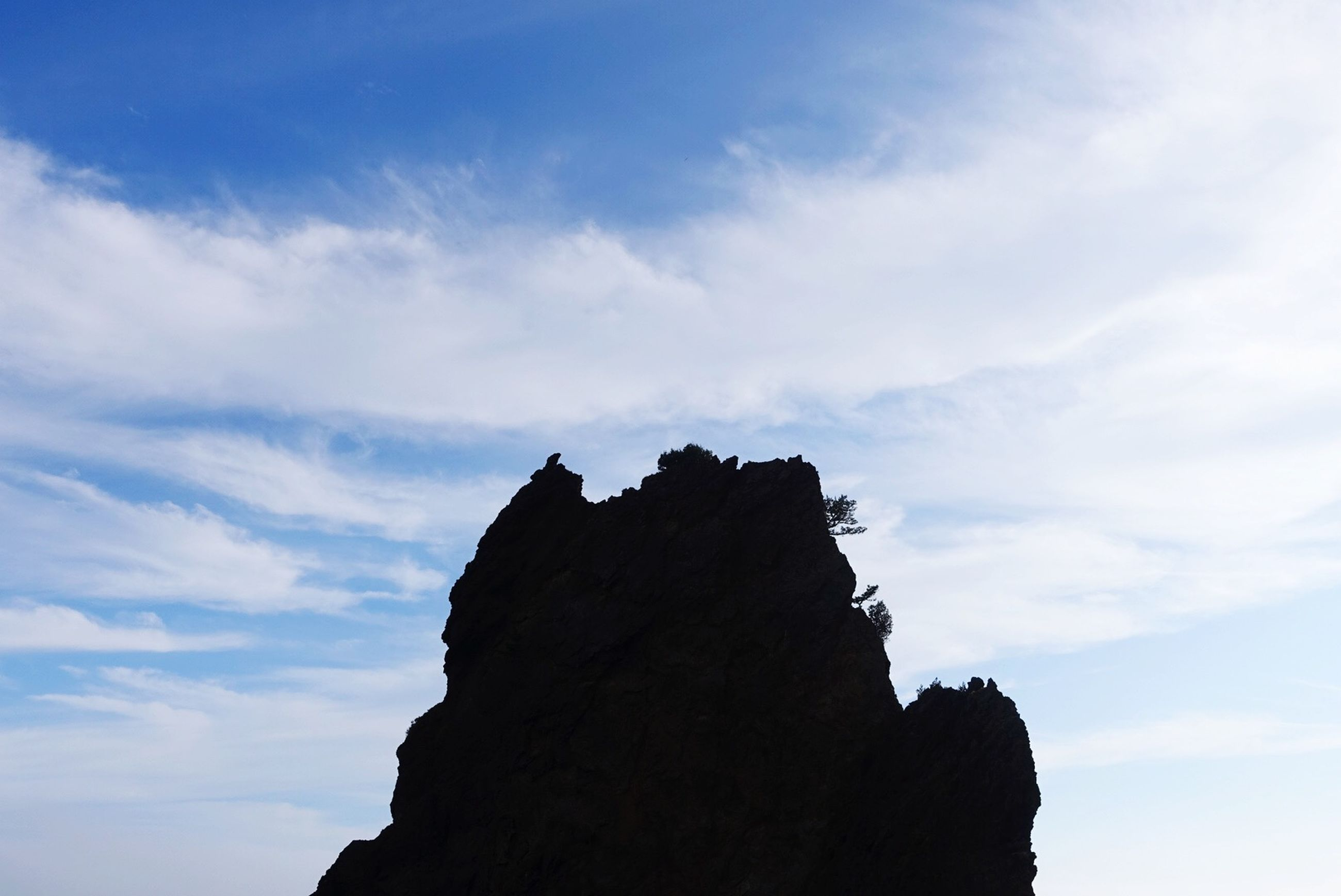 sky, low angle view, rock - object, rock formation, cloud - sky, tranquility, scenics, silhouette, nature, tranquil scene, beauty in nature, cloud, cliff, outdoors, day, blue, rock, no people, cloudy, rocky mountains