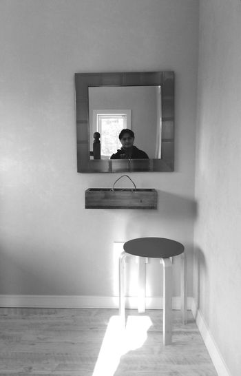Reflection of man in mirror mounted on wall
