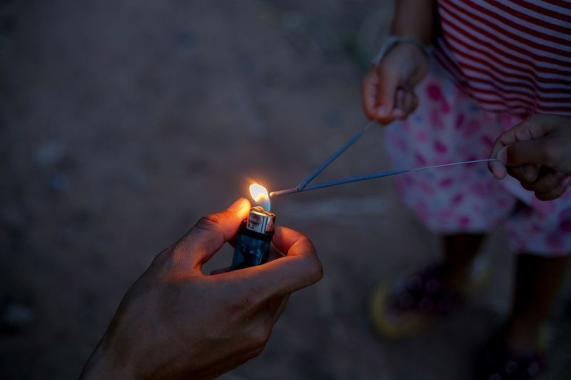 Cropped hand igniting sparklers held by girl