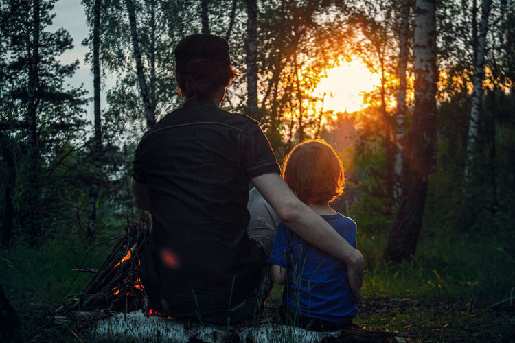 Rear view of two people sitting in the forest