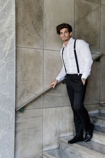 Portrait of man wearing suspenders while standing on steps