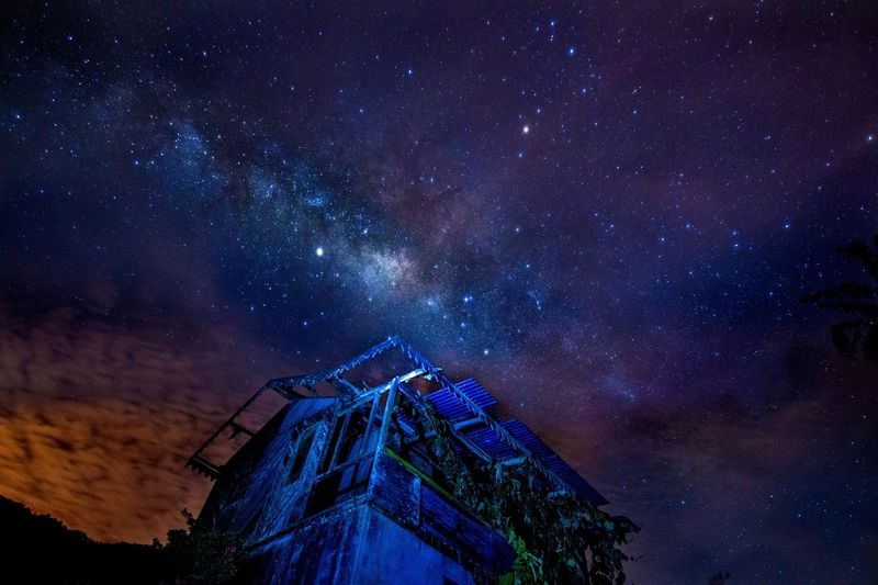 Low angle view of building against star field at night