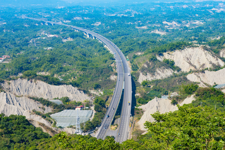 Aerial View Of Road Amidst Green Mountains