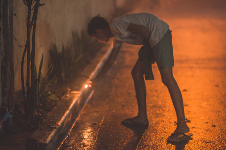 lighting a fire cracker! Dangerous Full Length One Person Real People Night Men Casual Clothing Lifestyles Bending Nature Road Motion Skill  Standing City Street Vitality Outdoors Transportation Land Bending Over Firecracker