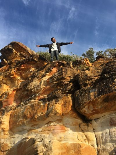 Low Angle View Of Young Man With Arms Outstretched Standing On Rock Against Blue Sky During Sunny Day