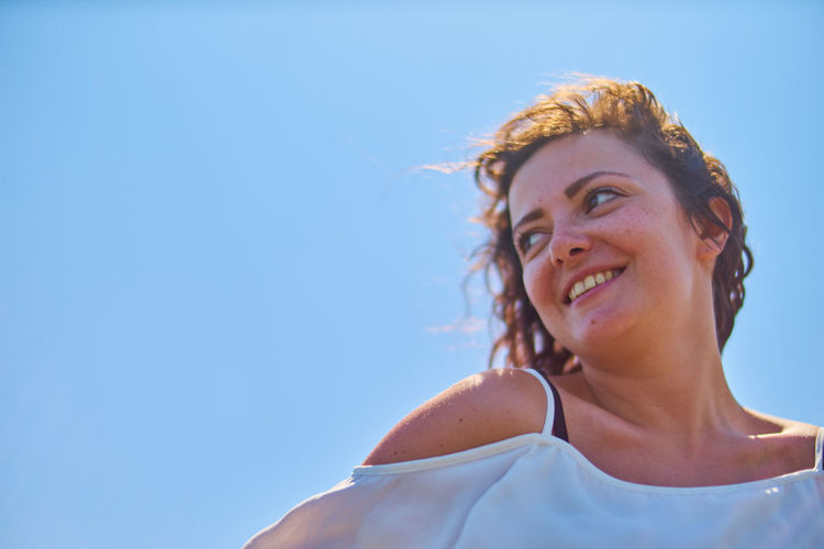 Low Angle Portrait Of Young Woman Against Clear Blue Sky