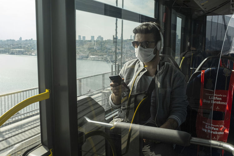 Man wearing mask using mobile phone in train