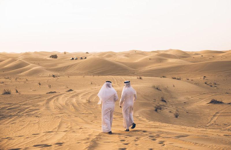 Rear view of men walking in desert against sky