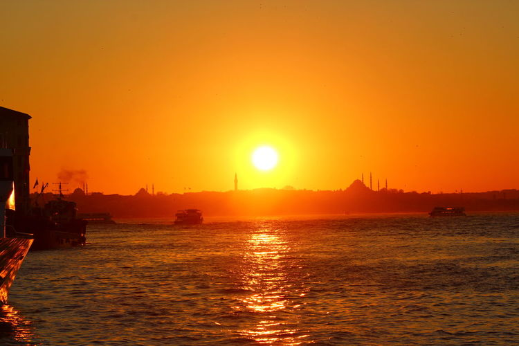River by suleymaniye mosque in background against orange sky