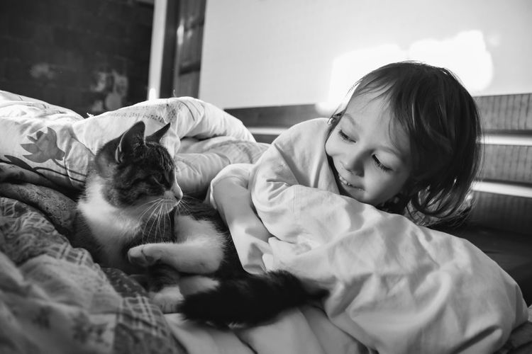 Boy sleeping with cat on bed at home