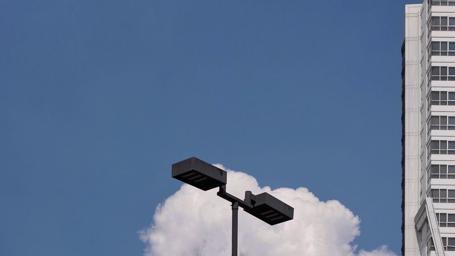 Black electric street light pole with white condominium building and white cloud.