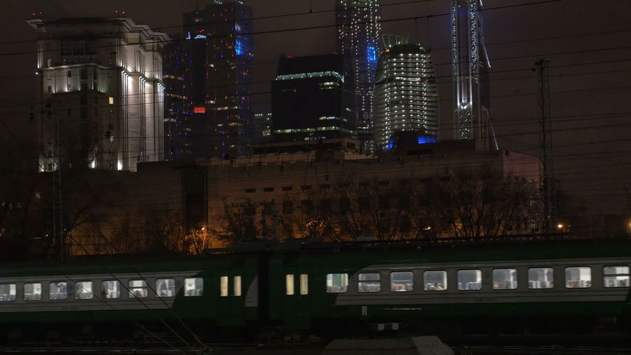 Illuminated railroad tracks by buildings in city at night