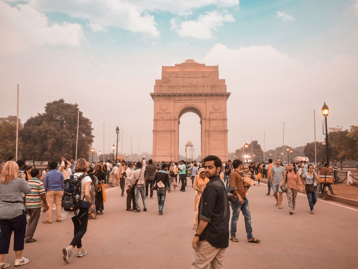 Man walking against india gate during sunset