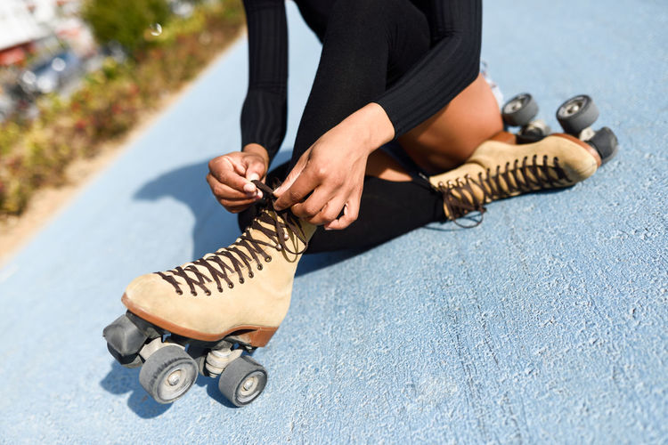 Close-up of black girl sitting on bike line and puts on skates. Unrecognizable woman. Rollerblading concept Roller Woman Young Adult Close-up Girl Human Body Part Human Leg Leisure Activity Lifestyles Low Section One Person Outdoors People Real People Road Rollerblading Rollerskates Sitting Skater Skatergirl Skates Sport Street Young Adult