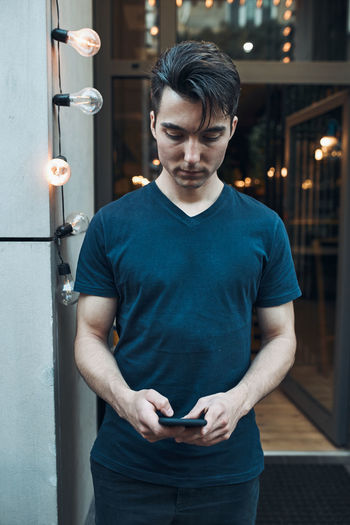 Young man using smart phone standing indoors