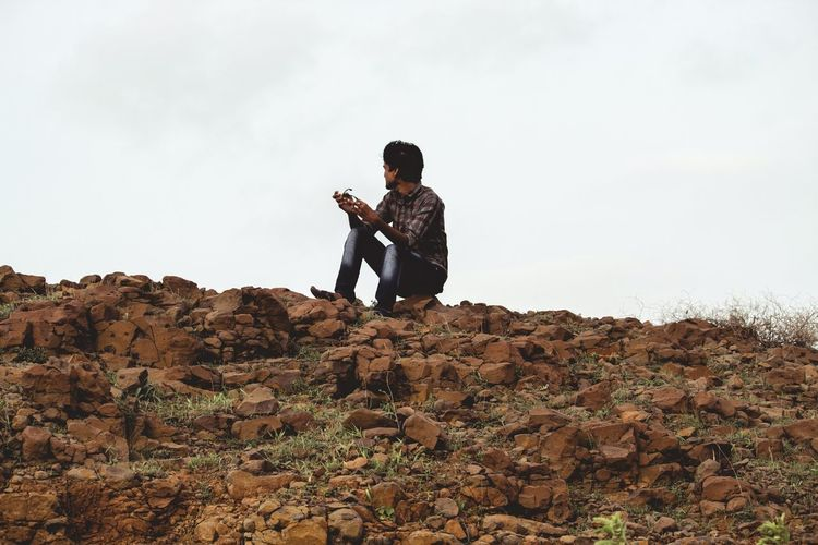 Side view of young man using mobile phone against sky