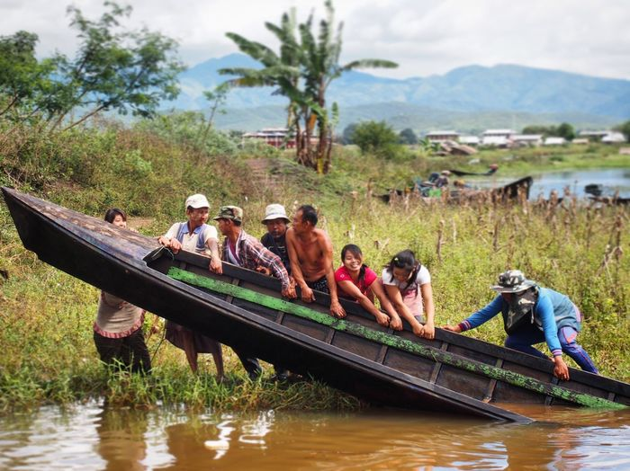 Men in boat on river against sky