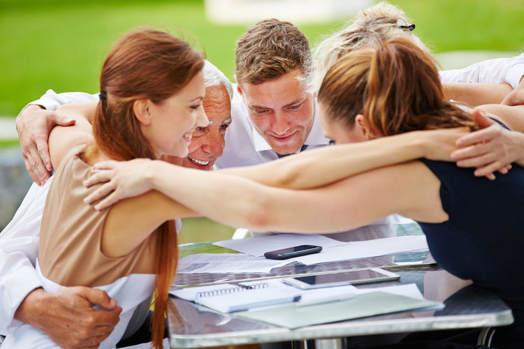 Business People Huddling At Table In Park