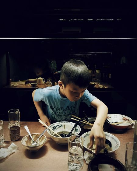 Boy Picking Chopsticks On Table At Home