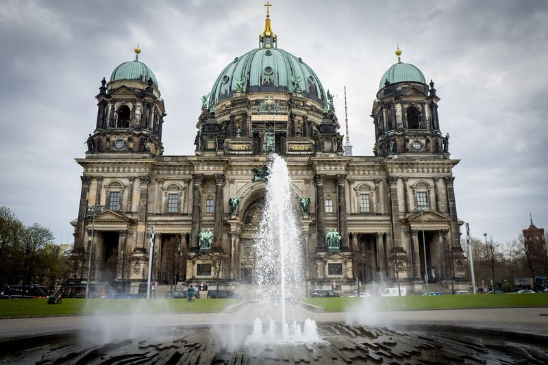 Fountain by berlin cathedral against sky