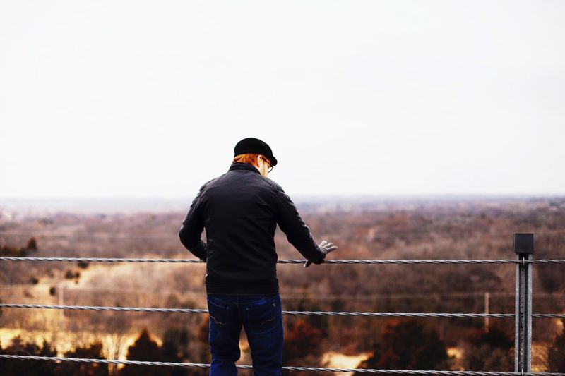 Rear view of man standing by railing against clear sky