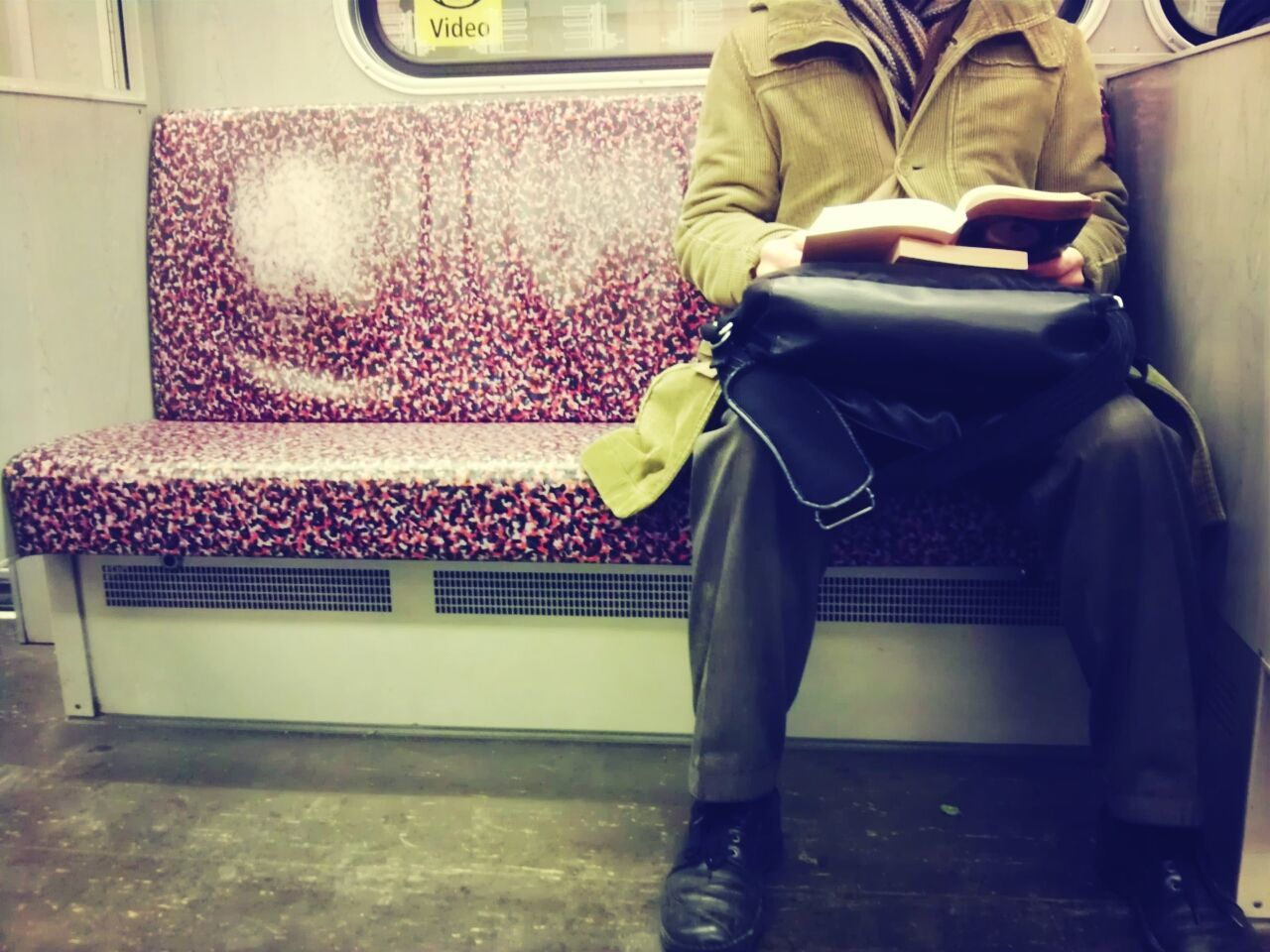 Low section of man reading book in bus