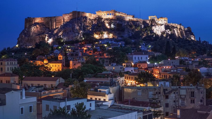 Buildings against acropolis of athens at night