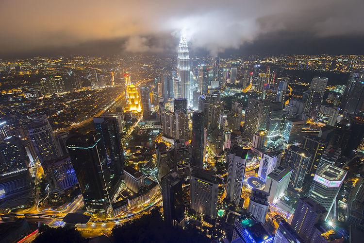 Petronas towers amidst illuminated cityscape against sky at night
