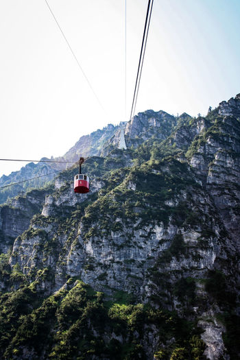 Low angle view of overhead cable car over mountains against sky
