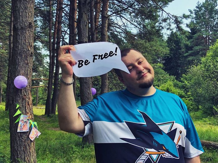 Young man holding be free speech bubble against trees