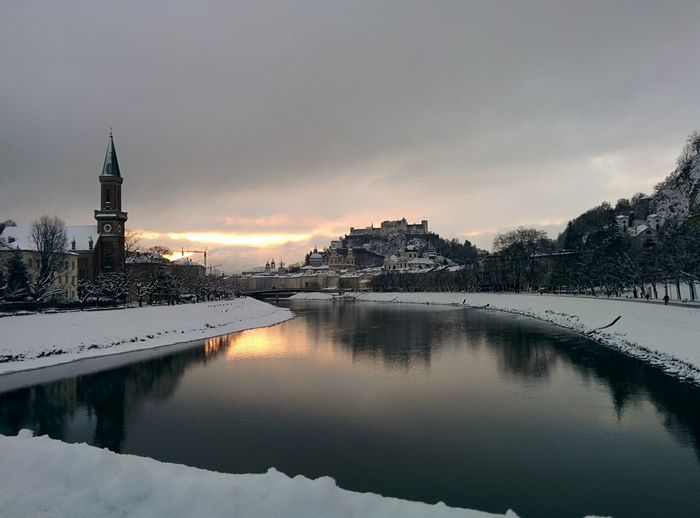 Scenic view of salzach river against cloudy sky during sunset
