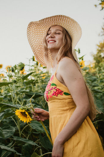 Young woman wearing hat standing against plants