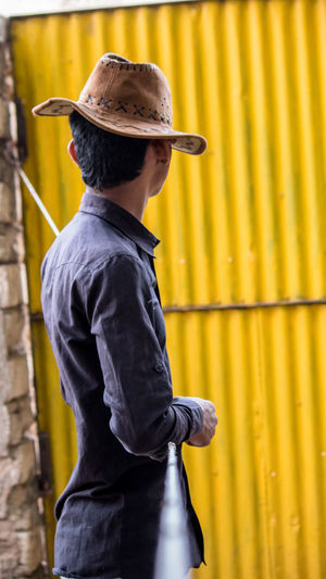 Teenage Boy Wearing Hat Against Metal Wall