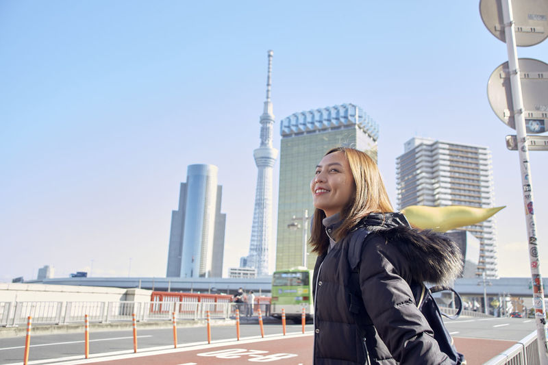 Young woman smiling while standing in city against clear sky