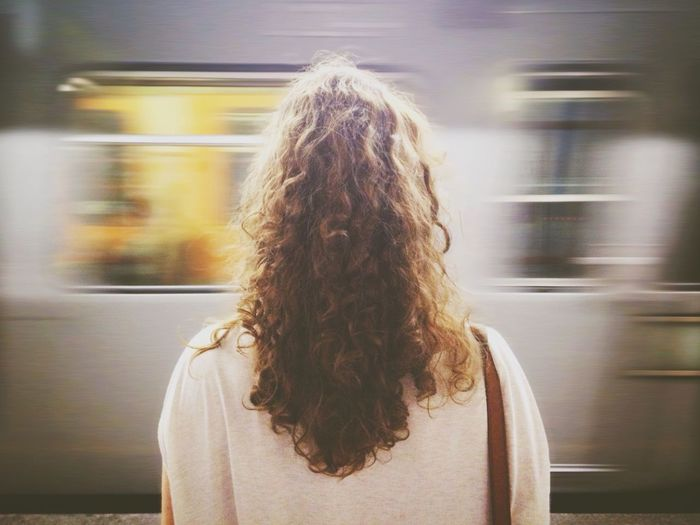 Rear view of young woman in front of train at station