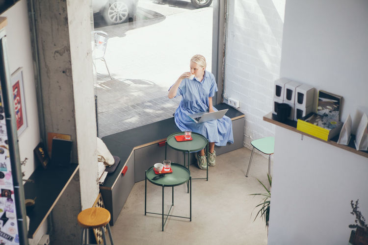 High angle view of woman drinking coffee while using laptop in cafe