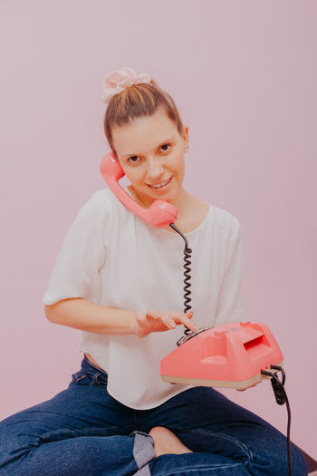 Portrait of smiling girl sitting against pink background