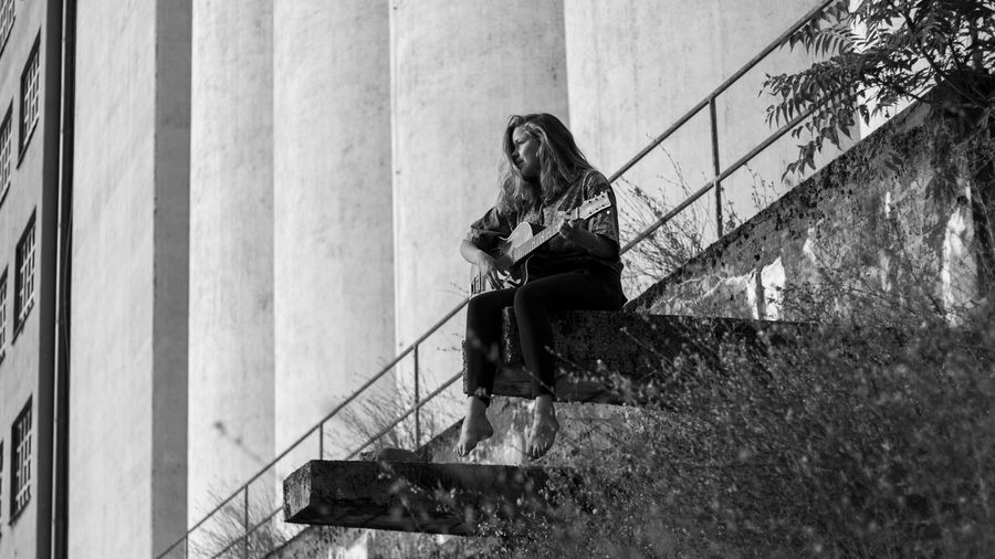 Low angle view of woman playing guitar while sitting against building