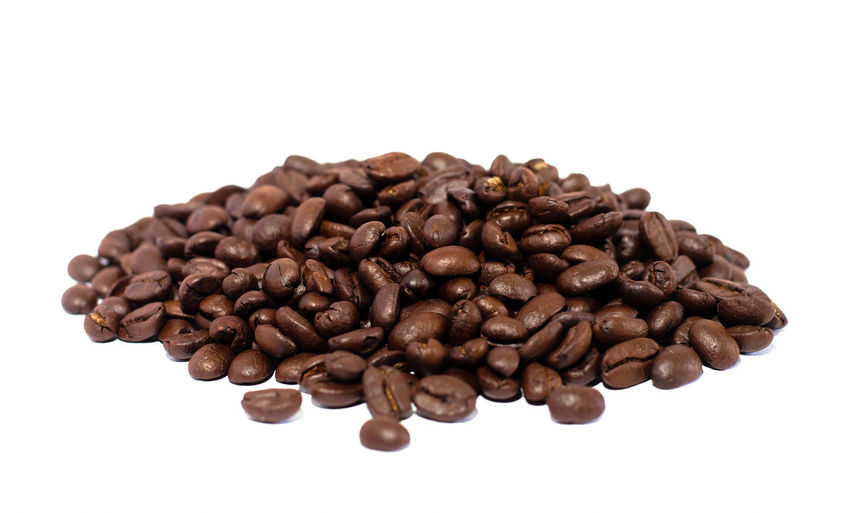 High angle view of coffee beans against white background