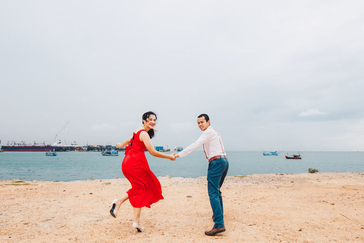 Rear View Of Couple Holding Hands While Standing On Beach Against Sky