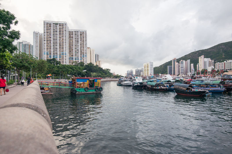 Boats in sea by buildings in city against sky