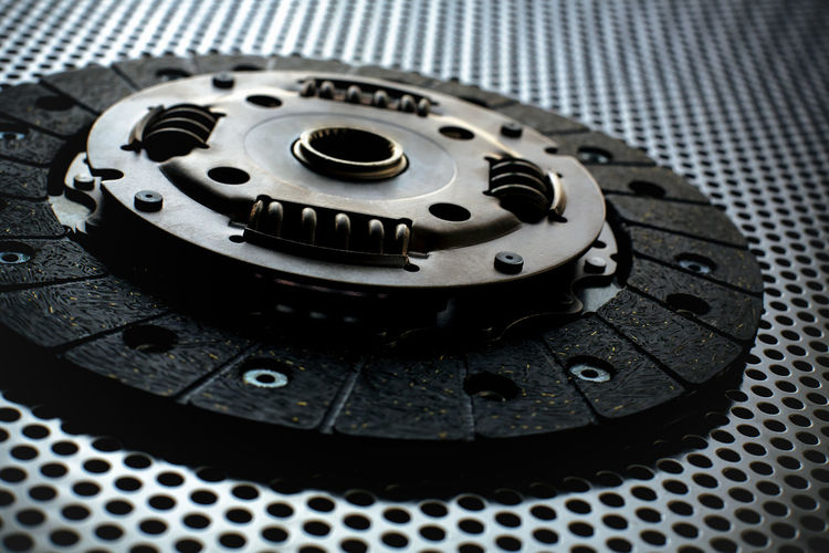 Car clutch on a metal surface. Photo from the classical vignetting effect it and a small depth of field Automobile Automotive Car Car Clutch Clutch Design Detail Disk Engine Gear Gearshift Machine Merchandise Metal Metallic Motor New Repair Replacement Service Spare Spring Steel Transmission Vehicle