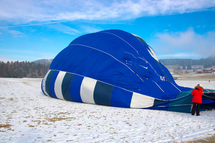 Rear view of man deflating hot air balloon after flight against cloudy sky