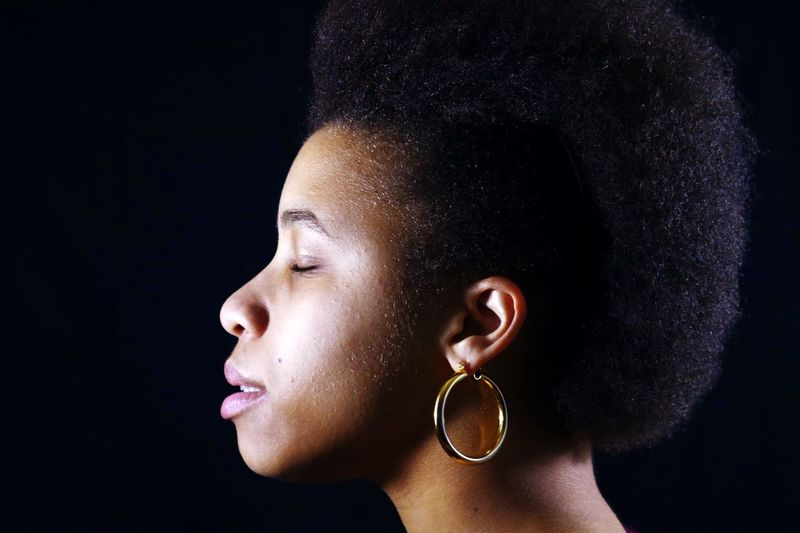 Profile View Of Young Woman With Curly Hair Against Black Background