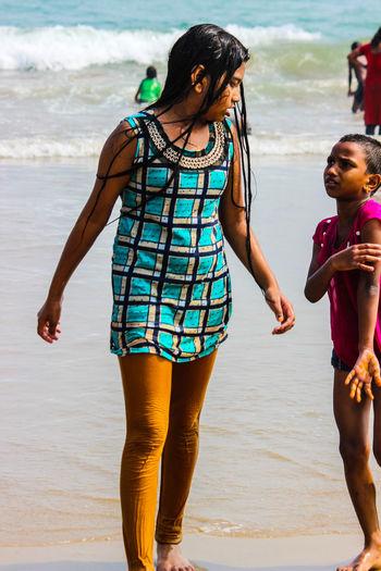 Full length of siblings walking at beach