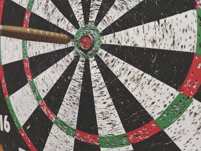 Full frame shot of dartboard with dart on bullseye